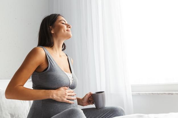 Zwangere vrouw binnenshuis thuis zitten poseren thee of koffie drinken op bed.