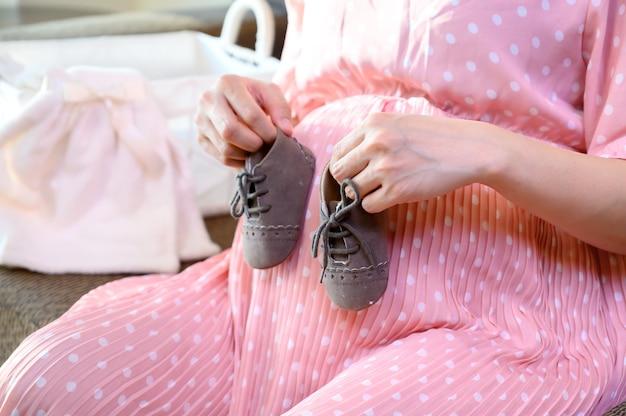 Zwangere vrouw blijft alleen thuis. zwangerschap op zoek naar een nieuwe baby die eraan komt.