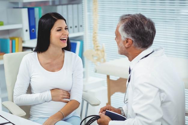 Zwangere vrouw die aan arts in kliniek spreekt