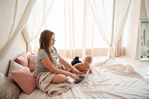 Zwangere vrouw die aan haar laptop werkt