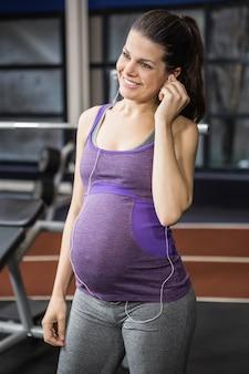 Zwangere vrouw die aan muziek bij de gymnastiek luistert