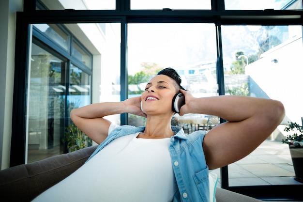 Zwangere vrouw die aan muziek op bank in woonkamer luistert