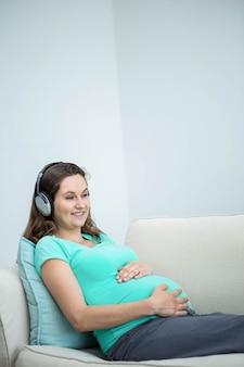 Zwangere vrouw die aan muziek op laag luistert