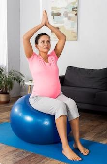 Zwangere vrouw die bal gebruikt om uit te oefenen