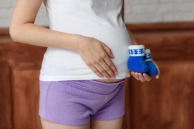 Zwangere vrouw die blauwe babybuiten op buik, close-up houdt