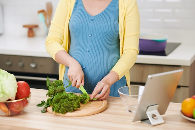 Zwangere vrouw die broccoli voor verse groene salade, gezonde voeding voor toekomstige moeder snijdt