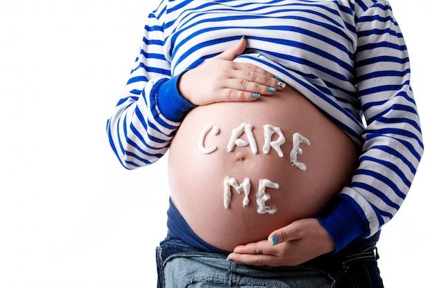 Zwangere vrouw die 'care me'-woord op haar buik schrijft. isoleren.