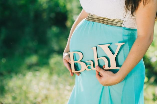 Zwangere vrouw die de baby voelt.