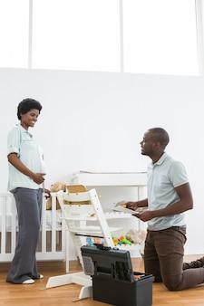 Zwangere vrouw die de mens bekijkt die een babystoel thuis bevestigt
