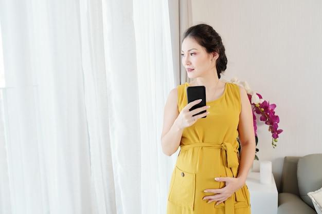 Zwangere vrouw die door venster kijkt