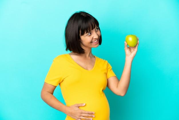 Zwangere vrouw die een appel vasthoudt die op blauwe achtergrond wordt geïsoleerd en een idee denkt terwijl ze omhoog kijkt