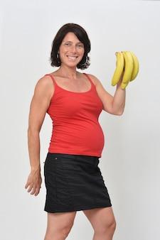 Zwangere vrouw die een banaan op witte achtergrond houdt