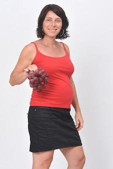 Zwangere vrouw die een druivenfruit op witte achtergrond houdt