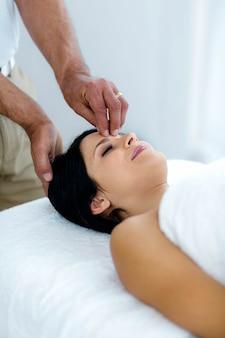Zwangere vrouw die een hoofdmassage thuis van masseur ontvangt