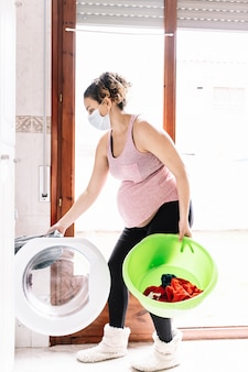 Zwangere vrouw die een masker in het gezicht draagt om virussen te voorkomen terwijl een wasmachine wordt geladen