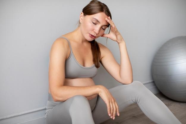 Zwangere vrouw die een pauze neemt van thuis sporten