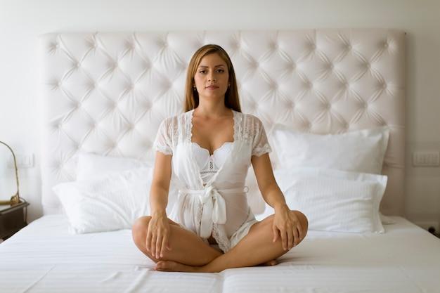 Zwangere vrouw die en yoga in haar slaapkamer mediteert praktizeert