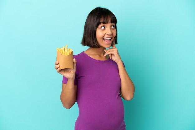 Zwangere vrouw die gefrituurde chips over een geïsoleerde achtergrond vasthoudt en een idee denkt terwijl ze omhoog kijkt