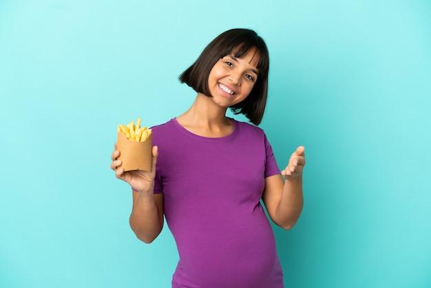 Zwangere vrouw die gefrituurde chips over een geïsoleerde muur houdt en handen schudt om een goede deal te sluiten