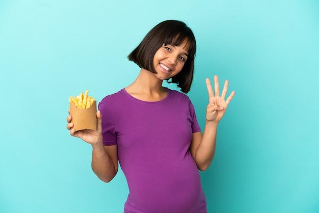 Zwangere vrouw die gefrituurde chips over geïsoleerde achtergrond gelukkig houdt en vier met vingers telt