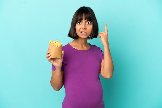 Zwangere vrouw die gefrituurde chips over geïsoleerde achtergrond houdt en een idee denkt