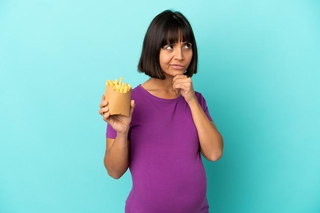 Zwangere vrouw die gefrituurde chips over geïsoleerde achtergrond vasthoudt en twijfelt