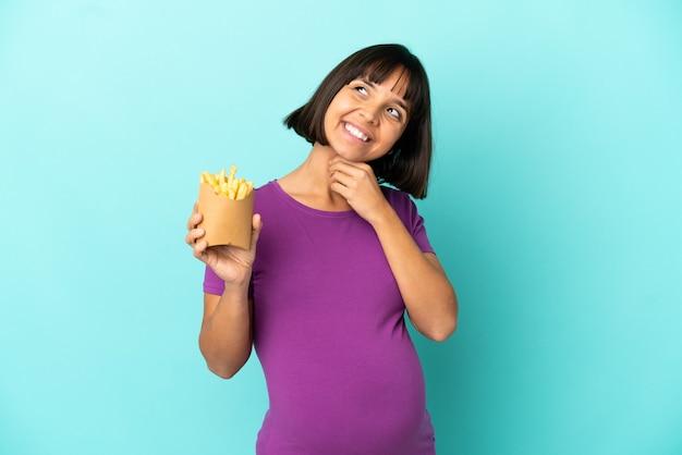 Zwangere vrouw die gefrituurde chips over geïsoleerde achtergrond vasthoudt terwijl ze glimlacht