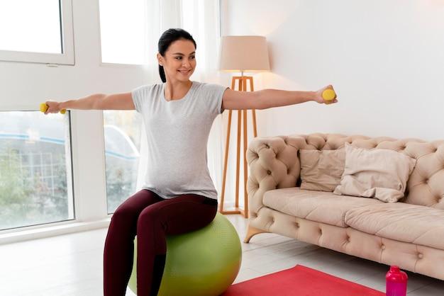Zwangere vrouw die gele gewichten met exemplaarruimte gebruikt