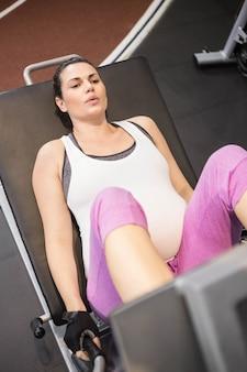 Zwangere vrouw die gewichtsmachine met behulp van bij de gymnastiek