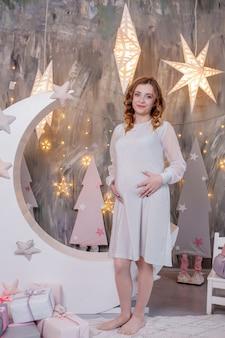 Zwangere vrouw die haar buik aanraakt in decoratiestudio met sterrenmaan motherhood