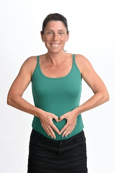 Zwangere vrouw die hartteken op haar buik op witte achtergrond doet