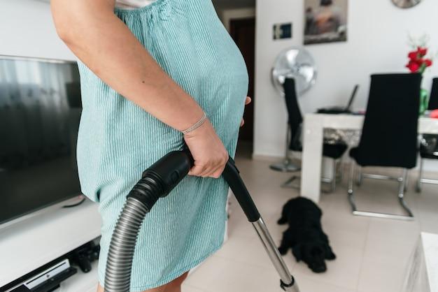Zwangere vrouw die het huis met stofzuiger schoonmaakt. hond onscherp op de achtergrond.
