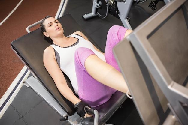 Zwangere vrouw die hometrainer met behulp van bij de gymnastiek