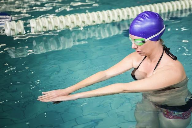 Zwangere vrouw die in de pool op het vrije tijdscentrum uitoefent