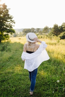 Zwangere vrouw die in het park met zonsondergang loopt