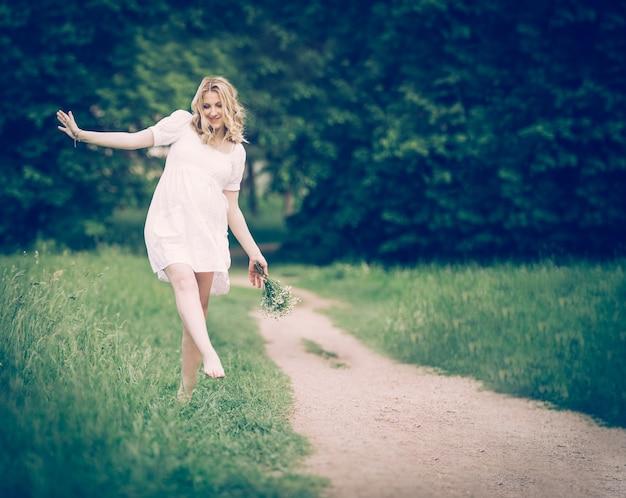 Zwangere vrouw die in het park op blote voeten op tapijt loopt, h