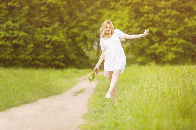 Zwangere vrouw die in het park op blote voeten op tapijt loopt,