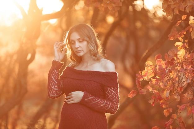 Zwangere vrouw die in rode lange kleding in de tuin loopt