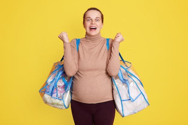 Zwangere vrouw die klaar is om naar de kraamkliniek te vertrekken, voelt zich gelukkig, wil sneller bevallen, uiting van opwinding, gebalde vuisten, casual kleding aan, houdt spullen vast voor het kraamhuis.