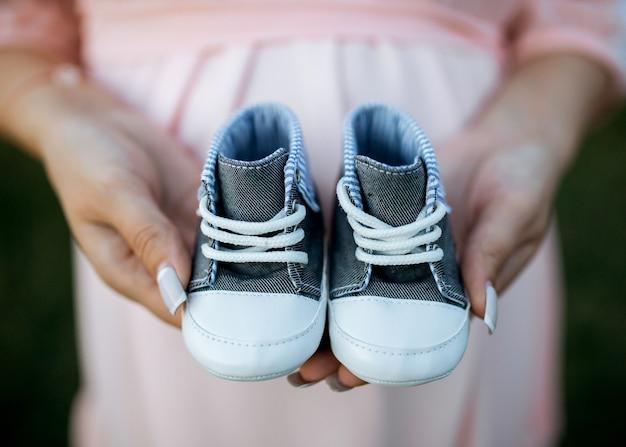 Zwangere vrouw die kleine babyslofjes houdt