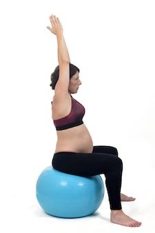 Zwangere vrouw die met een bal op witte achtergrond uitoefent