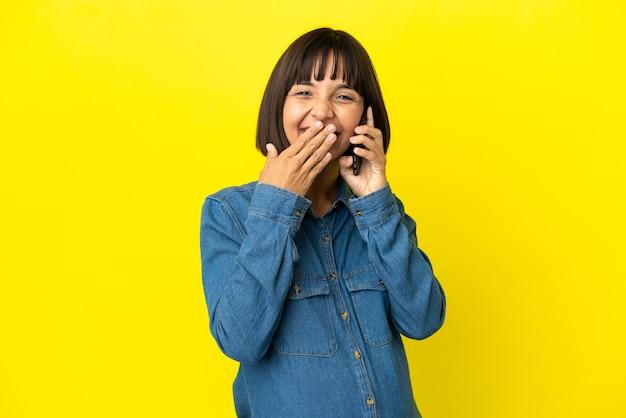Zwangere vrouw die mobiele telefoon gebruikt die op gele achtergrond wordt geïsoleerd gelukkig en glimlachend die mond met hand bedekken