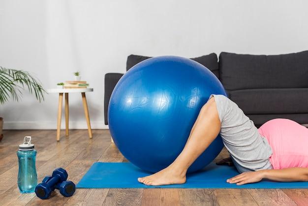Zwangere vrouw die oefeningsbal thuis gebruikt