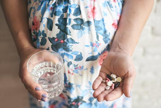 Zwangere vrouw die op baby wacht en vitaminen neemt