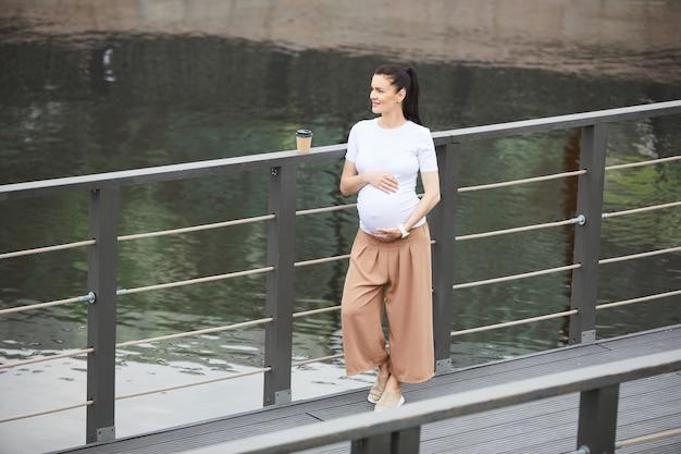 Zwangere vrouw die op de brug droomt