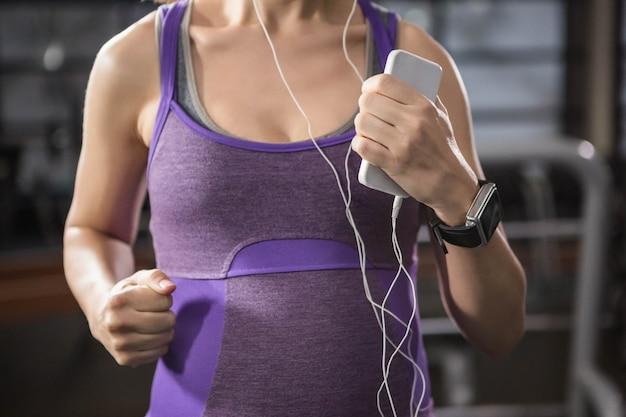 Zwangere vrouw die op een tredmolen uitoefent terwijl het luisteren aan muziek