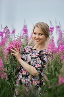 Zwangere vrouw die op gebied van bloemenwilgeroosje lopen, vrouw die en bloemen glimlachen plukken. de vrouw verwacht de geboorte van een baby in de negende maand van de zwangerschap