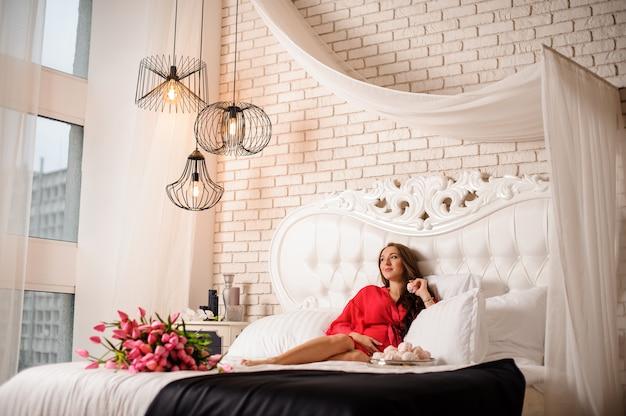 Zwangere vrouw die op het grote bed met een boeket van bloemen en snoepjes ligt