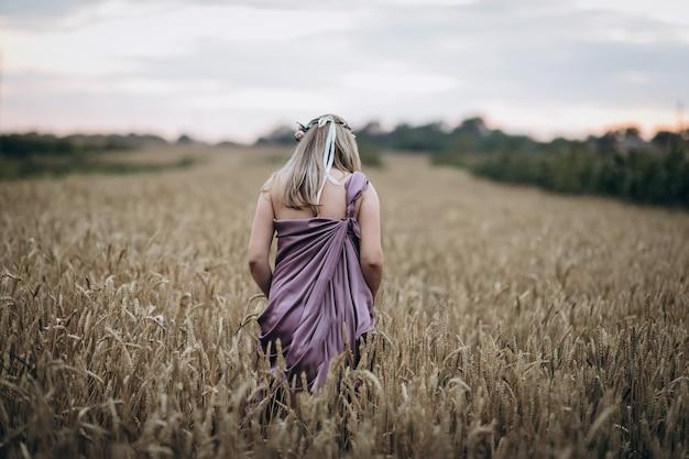 Zwangere vrouw die op het tarwegebied loopt