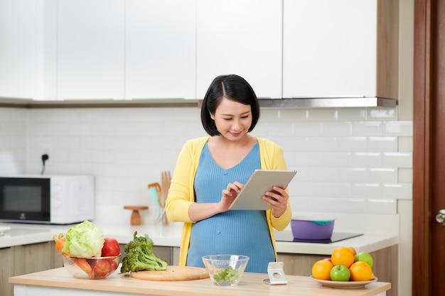 Zwangere vrouw die op keuken gezonde salade met digitale tablet maakt